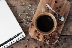 La taza de café caliente y el bosquejo blanco reservan en la tabla de madera Fotografía de archivo
