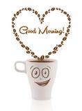 La taza de café con los granos de café formó el corazón con la muestra de la buena mañana Imagenes de archivo