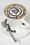 La taza de café grande adornada con espuma de la leche y el chocolate drenan Foto de archivo libre de regalías