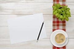 La taza de café y la planta interior están en un mantel a cuadros con el Libro Blanco, lápiz al lado de ellos Fotos de archivo libres de regalías