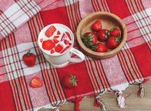 La taza de cerámica de yogur, las fresas frescas rojas está en la placa de madera en el mantel del control con la franja Salud or Foto de archivo libre de regalías