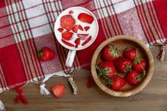 La taza de cerámica de yogur, las fresas frescas rojas está en la placa de madera en el mantel del control con la franja Sano org Imagen de archivo libre de regalías