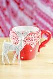 La taza de cocao caliente con los ciervos de la Navidad juega Imagen de archivo libre de regalías