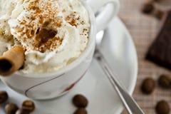 La taza de Coffe azotó la crema y los dulces Fotografía de archivo libre de regalías