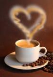 La taza de coffe con vapor tiene gusto del corazón Imagen de archivo libre de regalías