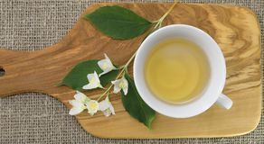 La taza de cristal blanca de té verde con el jazmín florece en fondo de madera verde oliva Visión superior Imagen de archivo