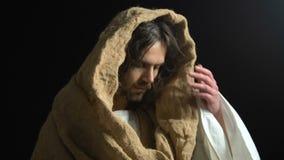 La taza de la demostración de Jesus Christ de agua contra fondo oscuro, gente sufridora ayuda almacen de metraje de vídeo