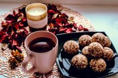 La taza de dulces del té mira al trasluz y subió los pétalos en la tabla fotos de archivo