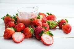 La taza de jugo de la fresa puso al lado de grupo de fresa roja imagen de archivo