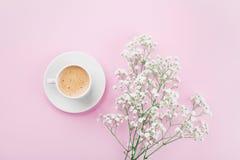 La taza de la mañana de café y las flores blancas en la opinión de sobremesa rosada en plano ponen estilo Desayuno hermoso para l Fotografía de archivo libre de regalías
