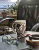 La taza de la mujer en el escritorio Foto de archivo