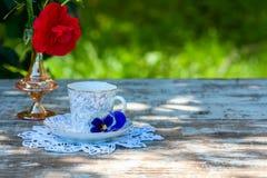 La taza de la porcelana de té y de primavera hermosa florece en florero en una tabla de madera en el jardín Partido del verano Foto de archivo libre de regalías