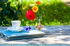 La taza de la porcelana de té y de primavera hermosa florece en florero en una tabla de madera en el jardín Partido del verano Fotografía de archivo libre de regalías