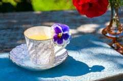 La taza de la porcelana de té y de primavera hermosa florece en florero en una tabla de madera en el jardín Partido del verano Imágenes de archivo libres de regalías