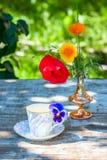 La taza de la porcelana de té y de primavera hermosa florece en florero en una tabla de madera en el jardín Partido del verano Fotografía de archivo