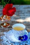 La taza de la porcelana de té y de primavera hermosa florece en florero en una tabla de madera en el jardín Partido del verano Fotos de archivo