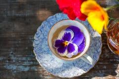 La taza de la porcelana de té y de primavera hermosa florece en florero en una tabla de madera en el jardín Partido del verano Imagen de archivo