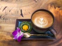 La taza de latte caliente del café con espuma en forma de corazón de la leche sirvió con Imagen de archivo libre de regalías