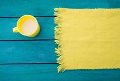 La taza de leche y la bufanda amarilla en una turquesa emergen Imágenes de archivo libres de regalías