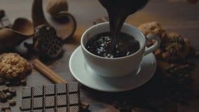 La taza de palillos de canela del café, las rebanadas del chocolate y el anís protagonizan en la tabla de madera vieja almacen de video