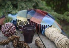 La taza de té caliente en una tabla de madera rústica con la decoración de conos, bramante, abeto ramifica Preparación para la Na Fotos de archivo libres de regalías