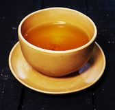 La taza de té china de la arcilla en tablero negro de la madera fotos de archivo