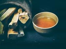 La taza de té china de la arcilla en tablero negro de la madera, al lado del bolso del cáñamo fotografía de archivo