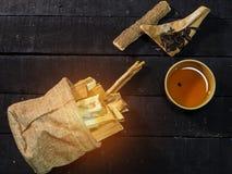 La taza de té china de la arcilla en tablero negro de la madera, al lado del bolso del cáñamo foto de archivo libre de regalías
