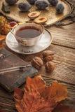 La taza de té con el regalo de la naturaleza y el cuaderno del vintage con la película filtran vertical del efecto Foto de archivo
