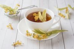 La taza de té con el tilo florece en una tabla ligera Imagenes de archivo