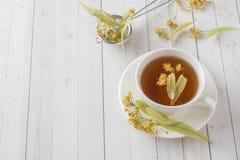 La taza de té con el tilo florece en una tabla ligera Fotografía de archivo