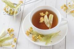 La taza de té con el tilo florece en una tabla ligera Fotos de archivo