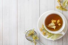 La taza de té con el tilo florece en una tabla ligera Imagen de archivo libre de regalías