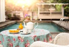 La taza de té con la fruta anaranjada de la rebanada fresca y el mollete se apelmazan en Foto de archivo libre de regalías