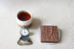 La taza de té con los brownie y el reloj es reloj del ` de cuatro o Imagen de archivo libre de regalías
