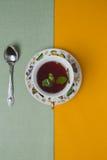 La taza de té con la menta está en una superficie plana del lino Fotos de archivo