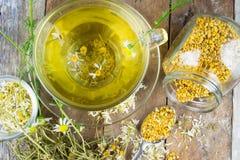 La taza de té de manzanilla con la manzanilla seca florece Imágenes de archivo libres de regalías