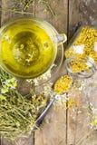 La taza de té de manzanilla con la manzanilla seca florece Fotografía de archivo