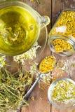La taza de té de manzanilla con la manzanilla seca florece Fotos de archivo libres de regalías