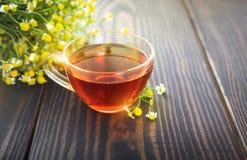 La taza de té de manzanilla y de un manojo de manzanilla florece en la tabla Fotos de archivo libres de regalías