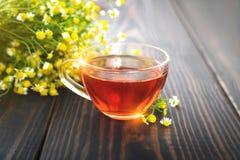 La taza de té de manzanilla y de un manojo de manzanilla florece en la tabla Imagen de archivo libre de regalías