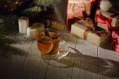La taza de té del invierno con el limón y el canela colocados en la tabla cubierta con las velas, los presentes envueltos y la Na imagen de archivo