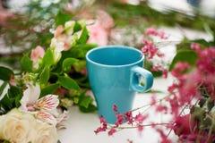 La taza de té en la tabla, se relaja Florista del taller, tabla con las flores, aún vida Foco suave Fotos de archivo