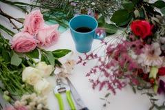 La taza de té en la tabla, se relaja Florista del taller, tabla con las flores, aún vida Foco suave Imagen de archivo libre de regalías