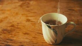 La taza de té es agua hirvienda vertida en la cámara lenta metrajes