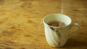 La taza de té es agua hirvienda vertida en la cámara lenta almacen de video