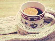 La taza de té caliente con el limón se vistió en bufanda caliente del invierno en fondo de madera Imagen de archivo