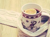La taza de té caliente con el limón se vistió en bufanda caliente del invierno en fondo de madera Imagenes de archivo