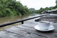 La taza del café con leche con el platillo puso una tabla de madera fotografía de archivo libre de regalías