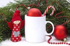 La taza del café con leche con las decoraciones y el pino de la Navidad ramifica Fotografía de archivo libre de regalías